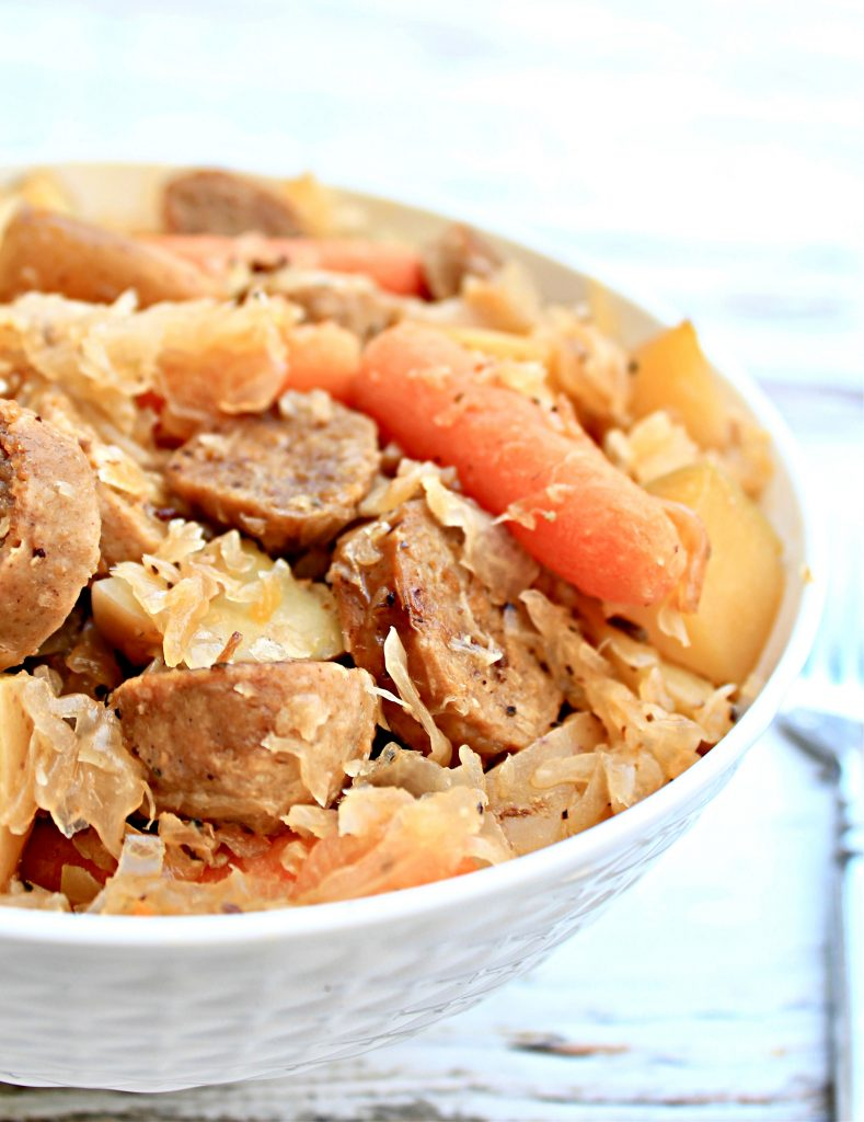 Crockpot Sausage and Sauerkraut ~ A hearty one-pot dinner with potatoes, carrots, garlic, onions, sauerkraut, and plant-based bratwurst.