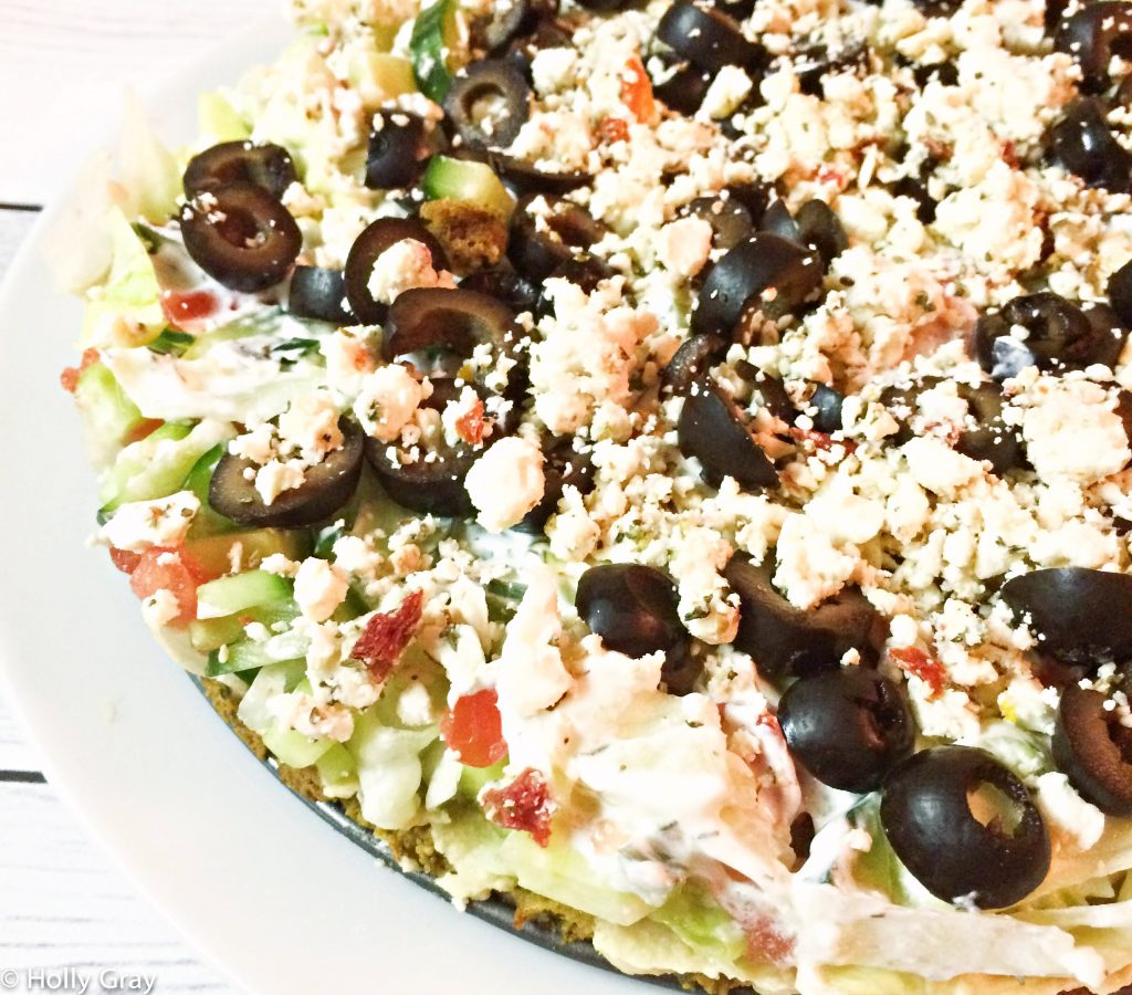 Baked Falafel Pie - A quick and easy meal with layers of falafel, hummus, tomatoes, cucumbers, lettuce, kalamata olives, feta, and tzatziki sauce.