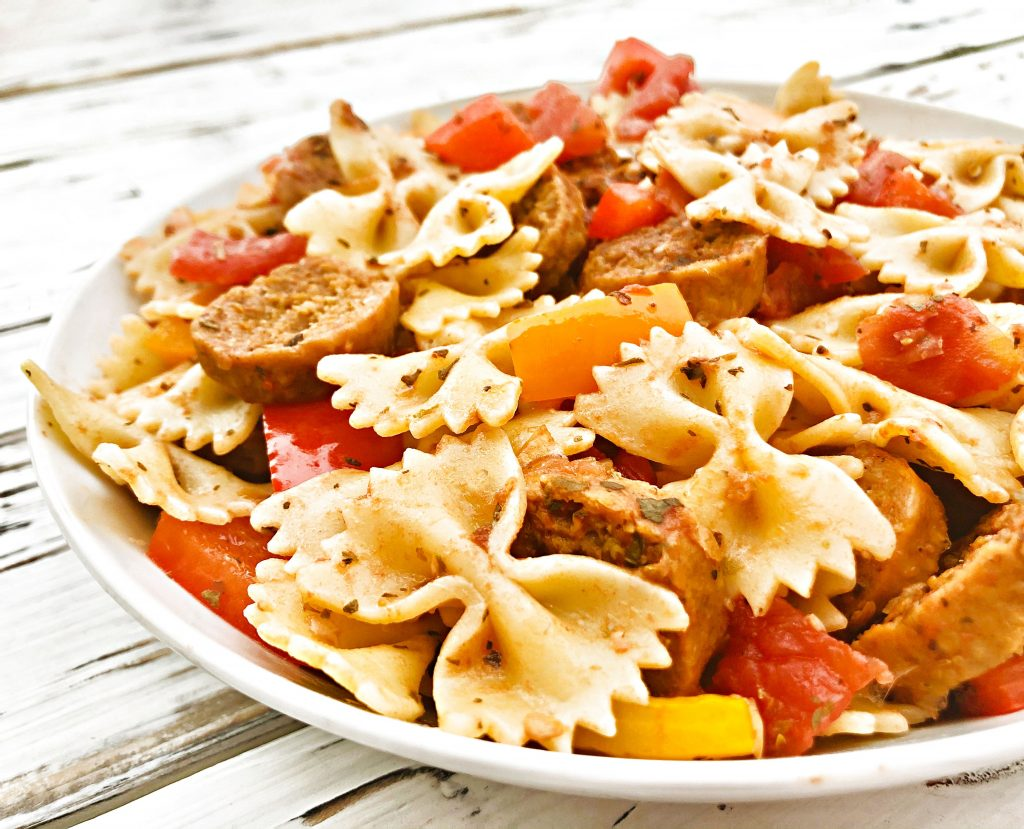 Vegan Sausage and Peppers Pasta - A quick and easy plant-based skillet dinner filled with spicy Italian sausage, colorful bell peppers, and pasta tossed together in a light and earthy tomato sauce. Ready to serve in 30 minutes or less! #sausageandpeppers #easyvegandinners #30minutemeals #vegansausagerecipes #thiswifecooksrecipes #quickandeasydinners #veganquarantinecooking #sausageandpepperspasta