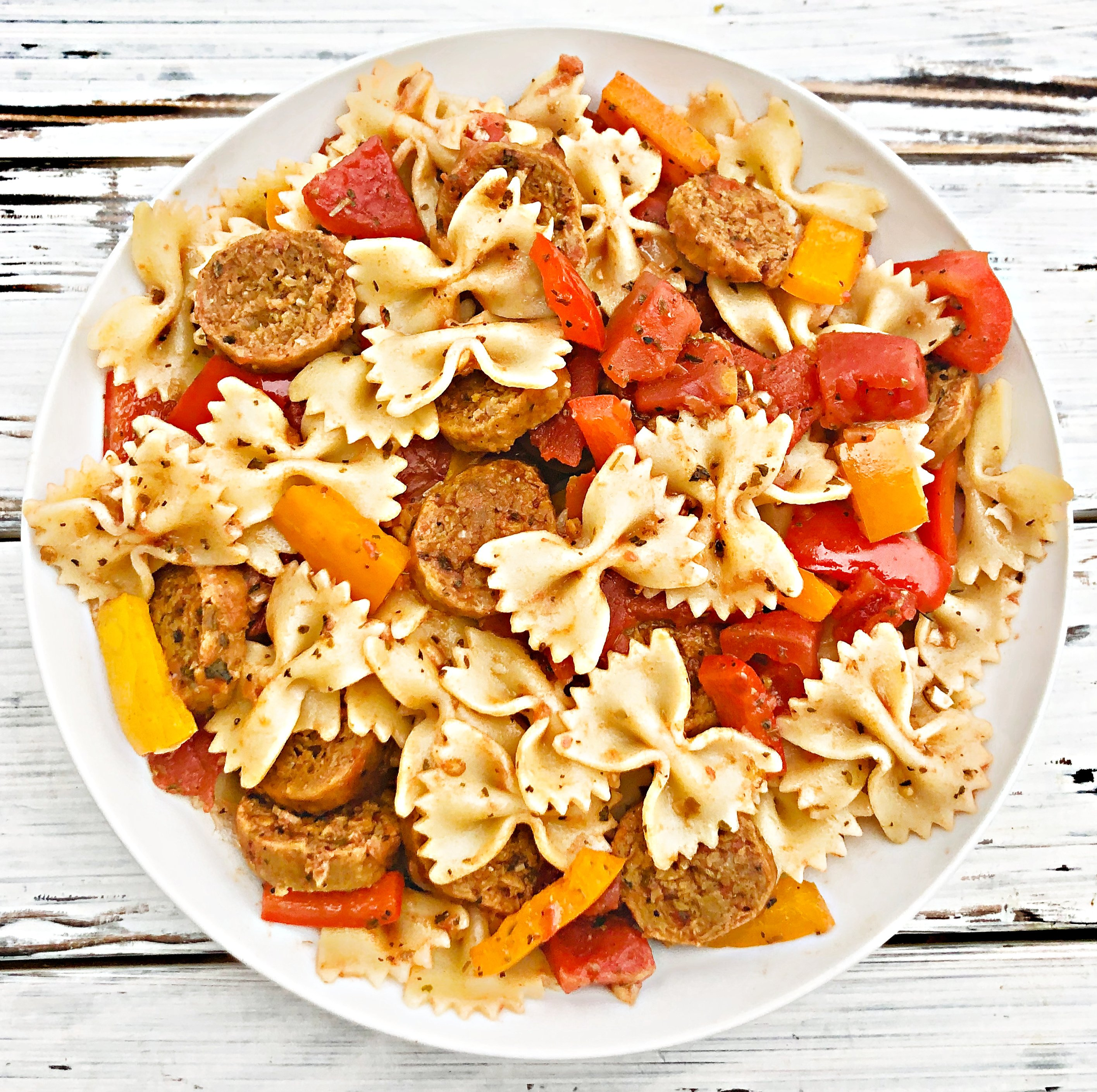 Vegan Sausage and Peppers Pasta - A quick and easy plant-based skillet dinner filled with spicy Italian sausage, colorful bell peppers, and pasta tossed together in a light and earthy tomato sauce. Ready to serve in 30 minutes or less!