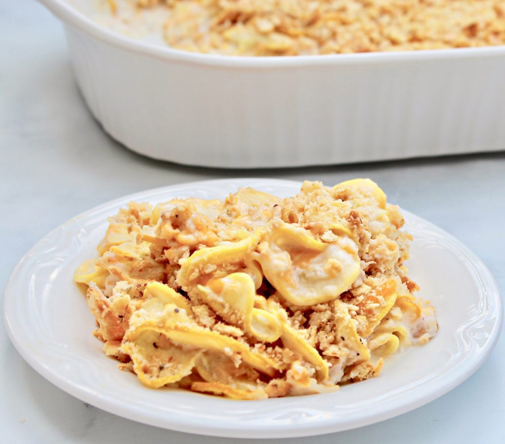 Yellow Squash Casserole ~ Sliced yellow squash baked in a creamy, cheesy sauce and topped with a simple and savory butter cracker crust. This Southern classic can be served as a main dish or side dish and is perfect for potlucks and barbecues.