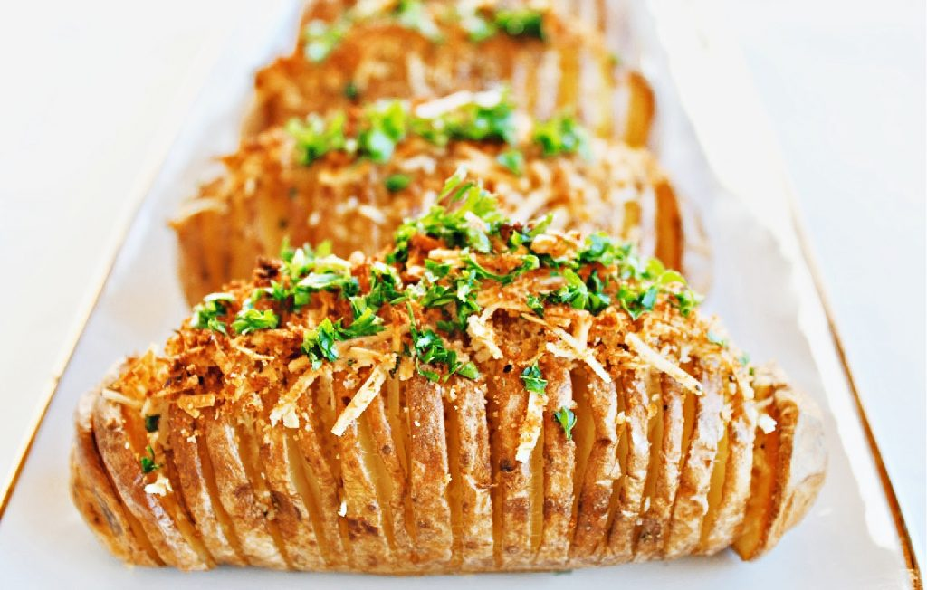 Hasselback Potatoes ~ Simple, savory, and perfect for holiday entertaining. These easy to make accordion-style baked potatoes are lightly crispy on the edges, creamy and buttery in the center, and topped with a mixture of dairy-free Parmesan and bread crumbs.