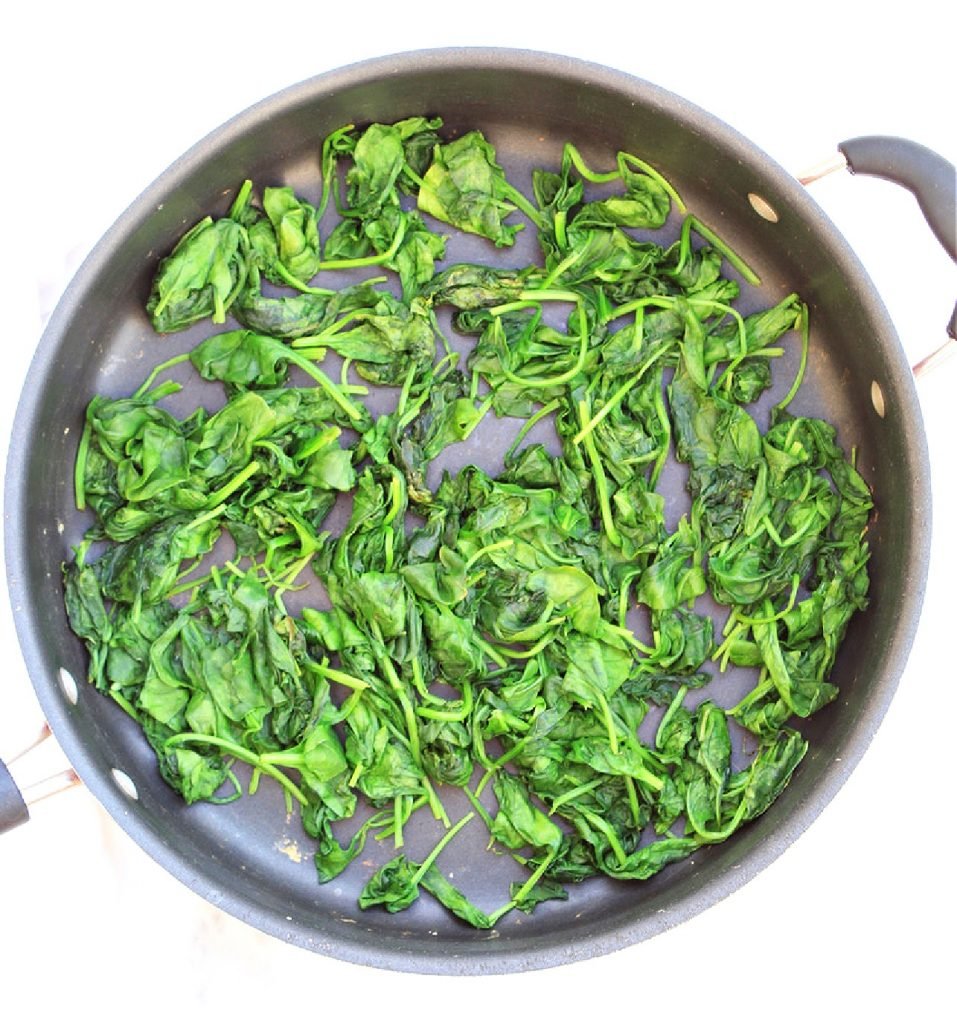 Wilted spinach leaves in skillet.