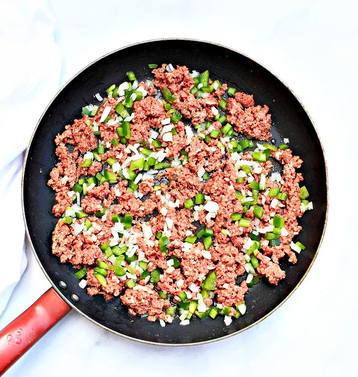 Skillet with vegan ground beef, bell pepper, and onion.