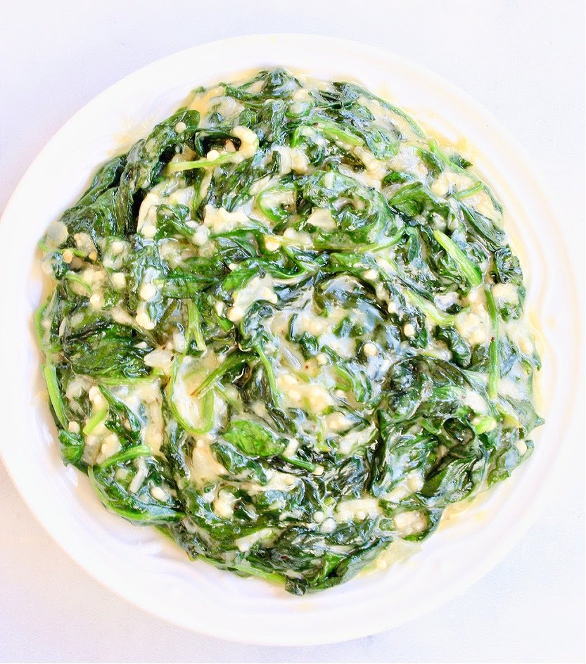 Top down view of vegan creamed spinach in white bowl.