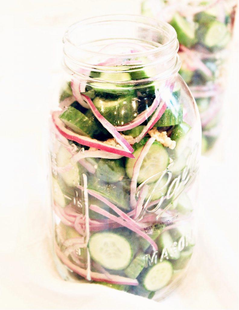 Cucumbers, red onion, and garlic stuffed into a glass jar.