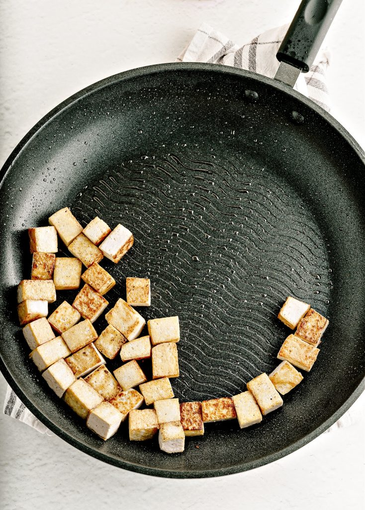 fried tofu cubes in black skillet