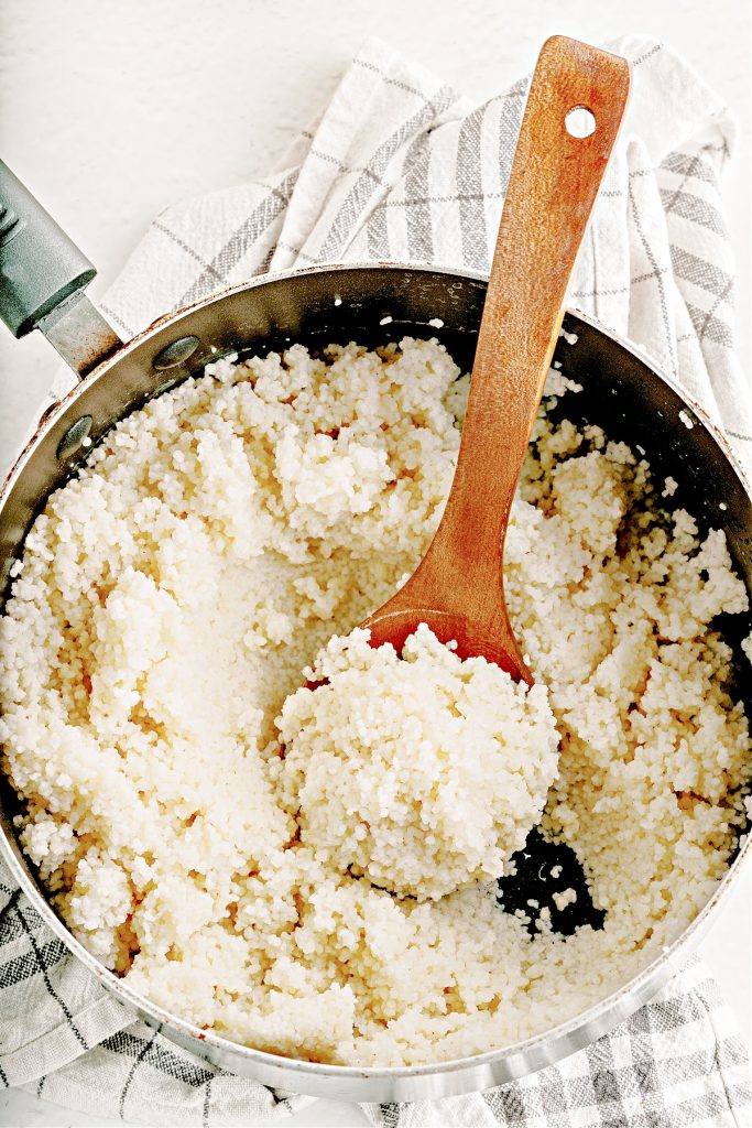 cooked couscous in pot with serving spoon