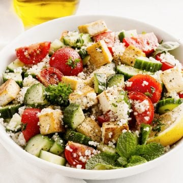 herbed couscous and tofu salad in white bowl in white bowl
