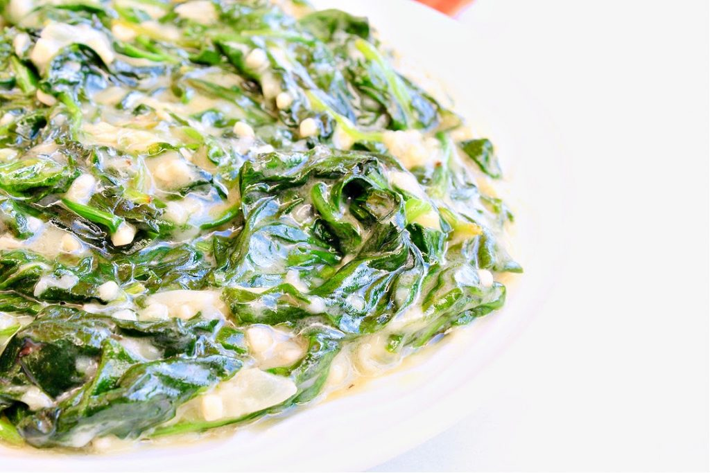 Side view of vegan creamed spinach in white bowl.