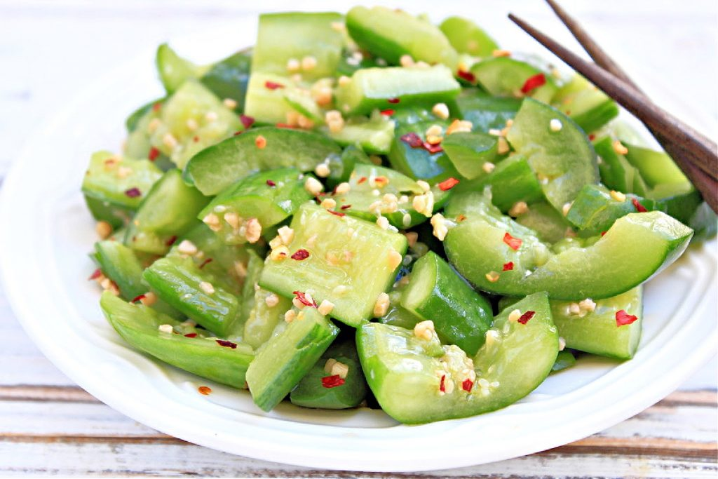 smashed cucumber salad in bowl with chopsticks