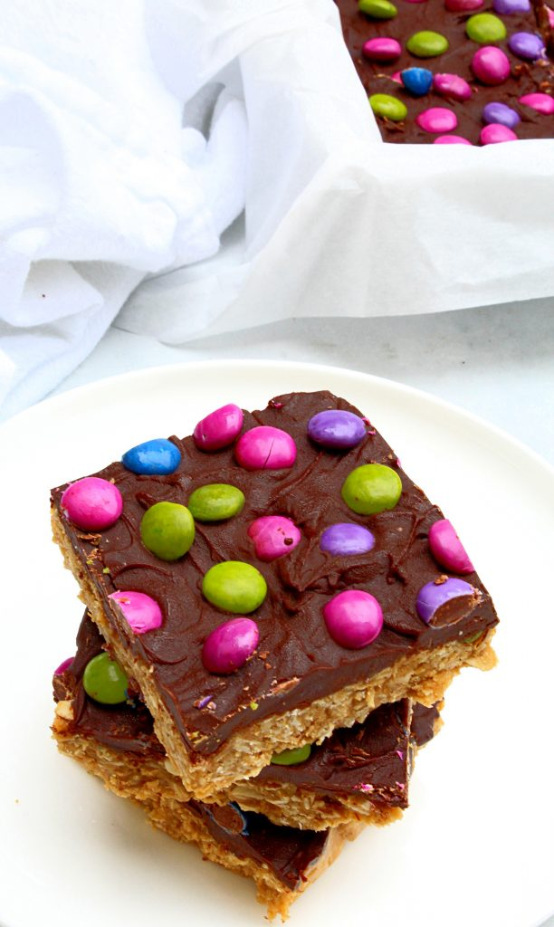 Vegan Monster Cookie Bars ~ Peanut butter and oatmeal cookie dough smothered in chocolate and studded with colorful candies is an easy, no-bake dessert treat that is frightfully delicious!